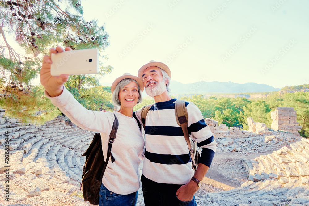 Fototapeta Tourism and technology. Traveling senior couple taking selfie together against ancient sightseeing background.