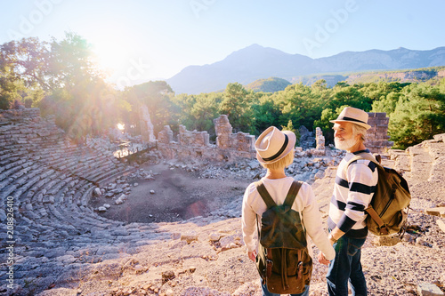 Travel and tourism. Senior family couple enjoying view together on ancient amphitheatre.