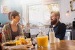 Cheerful couple having breakfast in the kitchen of their house