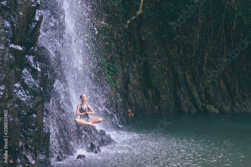 Wellness spa, vacation and yoga meditation concept. Pretty young woman in swimsuit sitting in lotus position on the rock under tropical waterfall.