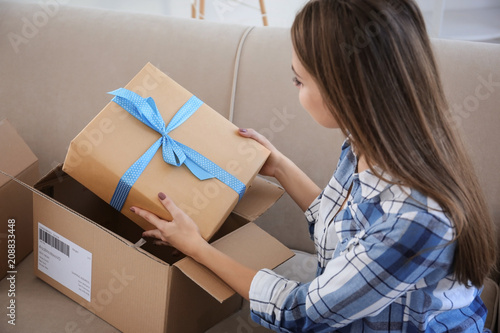 Obraz Young woman opening parcel at home - fototapety do salonu