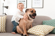 Cute little child with dog on couch at home
