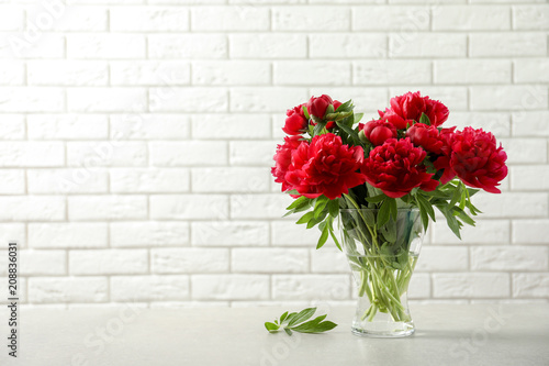 Vase with beautiful blooming peonies on table near brick wall