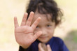 Boy with an open palm gesture that means stop