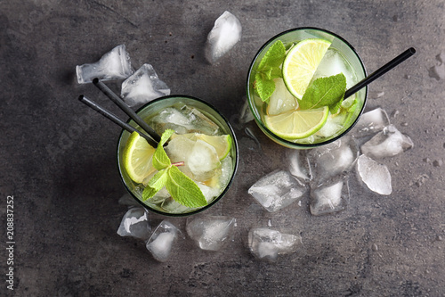 Flat lay composition with mint julep cocktail and ice cubes on grey background Canvas-taulu