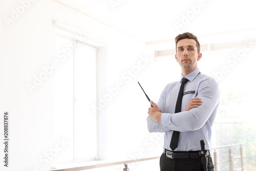 Male security guard with portable radio transmitter indoors Wallpaper Mural