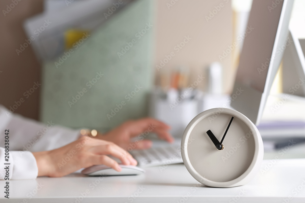 Fototapety, obrazy: Alarm clock and blurred woman working on background. Time management