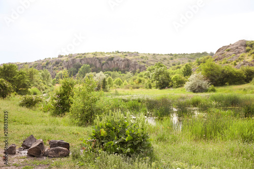 Foto op Plexiglas Pistache Beautiful landscape with beautiful pond and rocky hill. Camping season