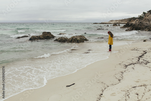 Foto op Plexiglas Strand Girl in raincoat on the beach in winter.