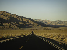 Long Paved Road Into The Mountains With Red Truck Driving In Distance