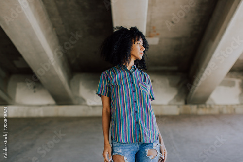 A beautiful African American woman in the city standing under a highway underpass.