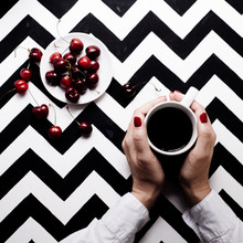 Mug With Coffee In Hands, And Cherry On A Black-and-white Background