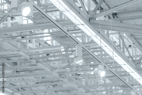 Staande foto Industrial geb. row of bright halogen spotlights on exhibition ceiling. industrial building interior
