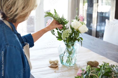 Senior Woman Arranging Flowers In Vase On Table Buy This Stock