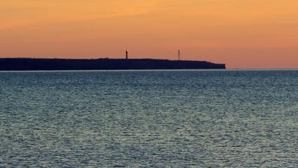 Latarnia morska świecąca po zmroku na estońskim klifie wystającym na morzu bałtyckim