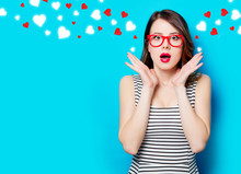 Portrait Of Beautiful Surprised Young Woman In Glasses On The Wonderful Blue Studio Background And Abstract Hearts