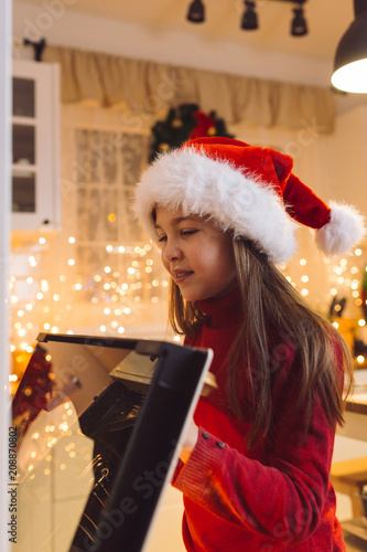 Girl waiting for fresh baked Christmas cookie