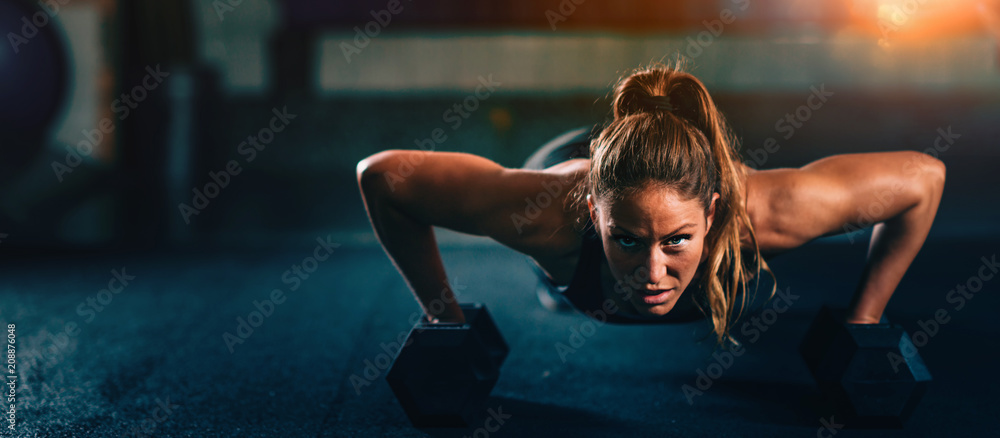 Fototapeta Cross training. Young woman exercising at the gym