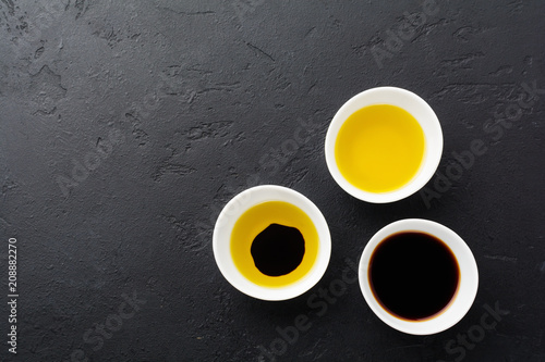Soy sauce, olive oil and balsamic sauce in white ceramic bowls on black stone or concrete background.