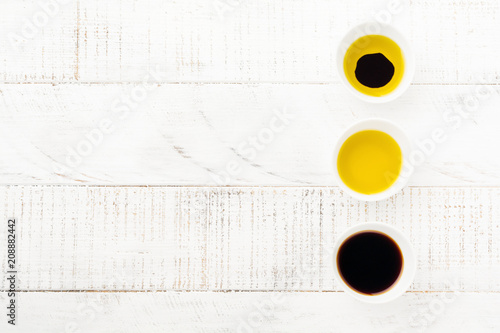 Soy sauce, olive oil and balsamic sauce in ceramic bowls on white wooden background. Top view.