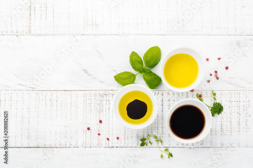 Soy sauce, olive oil and balsamic sauce with herbs basil, parsley, pepper and thyme on white wooden background. Top view.