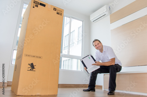 Fototapeta A man holding documents sits beside a large package in an empty room. The postman delivers the parcel to the new apartment. obraz