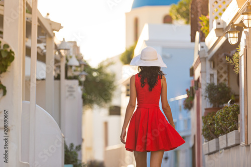 Foto op Plexiglas Europa Santorini travel tourist brunette woman in red dress visiting famous white Oia village.