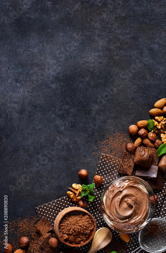 Spoed Foto op Canvas Dessert Black food background with cocoa, nuts and chocolate paste. top view