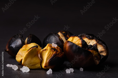Fotografie, Obraz  Closeup of roasted chestnuts with grains of salt on a black background