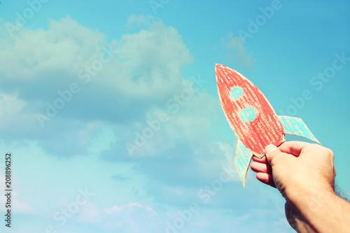 Obraz na plátně  image of male hand holding a rocket against the sky