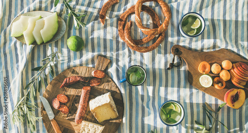 Photo sur Toile Pique-nique Flat-lay of summer picnic set with fruit, cheese, sausage, bagels and lemonade over striped blanket, top view