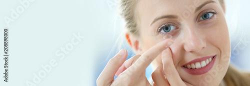 Fotografía  Young woman putting eye contact lense on, template