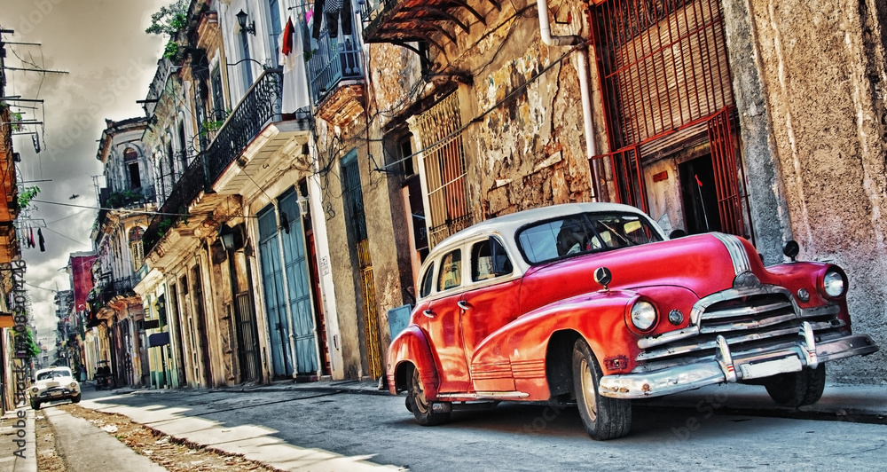 Fototapeta old american car parked with havana building in background