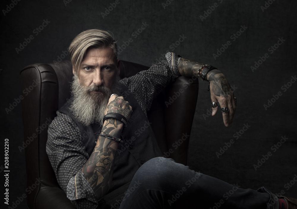 Fototapeta Porträt eines tätowierten bärtigen Mannes, der in einem Sessel sitzt