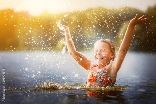 little girl playing in the river. A girl with blond hair raises her hands up in the water and splashes water drops