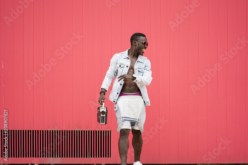 African man red background with vintage radio device.