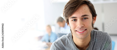 Portrait of smiling student in school class, template