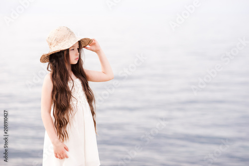 Fotografiet  Pretty kid girl 4-5 year old wearing hat and dress over sea background