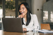 Photo of cheerful asian woman 20s wearing white shirt laughing and pointing finger at screen of laptop, while speaking or chatting on video call in office