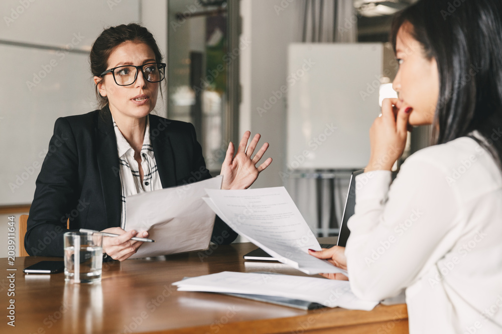 Fototapeta Photo of strict caucasian woman holding resume, and negotiating with female candidate during corporate meeting or job interview - business, career and placement concept