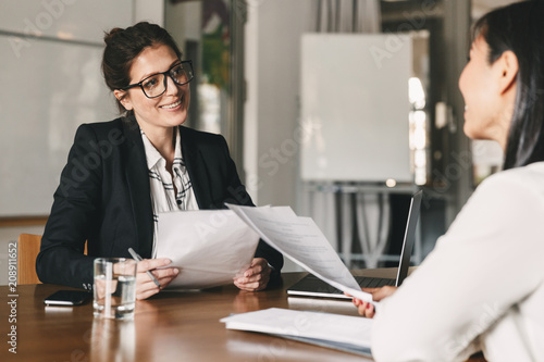 Portrait of smiling businesswoman holding resume and talking to female candidate Canvas Print