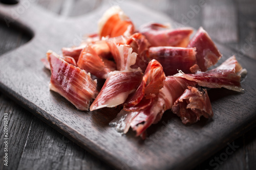 Photo  Traditional Spanish Jamon Serrano ham, Prosciutto Crudo, Parma ham, Italian antipasto