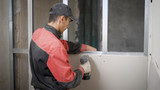 Fototapeta Łazienka - repairman is fixing a gypsum board on profiles, using self-tapping screws and electrical screwdriver
