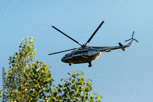 Tuinposter Helicopter civil helicopter in the air against the sky and green tree