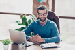 canvas print picture - Stunning, smiling, harsh, virile, IT-manager in glasses, pullover, shirt, sitting on leather chair at desktop in workplace, looking at camera
