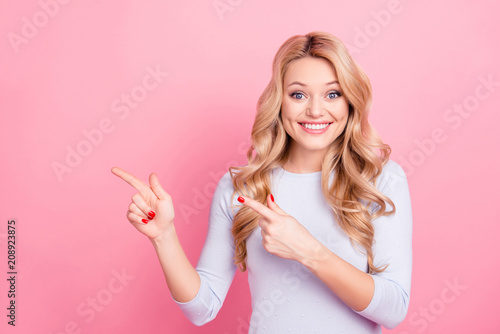Portrait of charming toothy girl in pullover with beaming smile pointing two forefingers to copyspace empty place looking at camera isolated on pink background