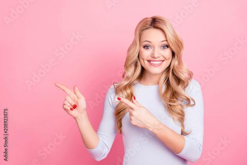 Fototapeta premium Portret uroczej zębatej dziewczyny w swetrze z promiennym uśmiechem wskazującym dwoma palcami wskazującymi na puste miejsce, patrząc na aparat odizolowany na różowym tle