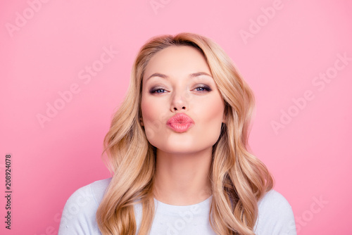 Fotografie, Tablou  Portrait of cute lovely girl in casual outfit with modern hairdo sending blowing kiss with pout lips looking at camera  isolated on pink background
