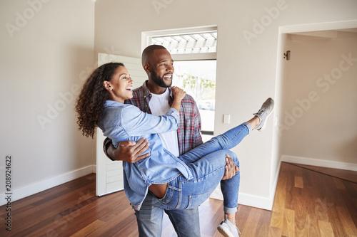 Fototapeta Man Carrying Woman Over Threshold Of Doorway In New Home obraz