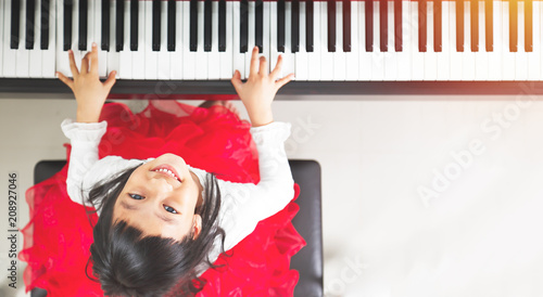 Fotografie, Obraz  Little asian girl happy to play piano